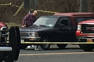 Behind the crime tape in New Milford a pickup truck with its driverside window blown out.