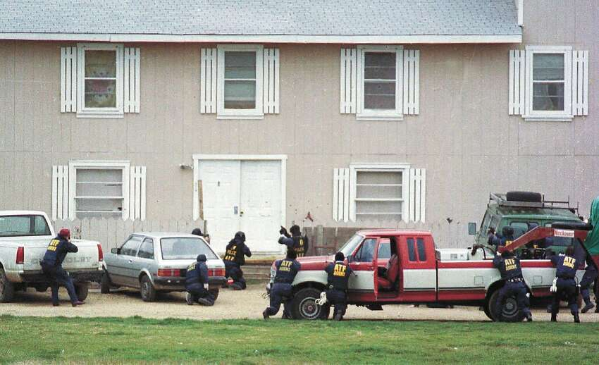 Federal Alcohol Tobacco and Firearms agents approach the front door of the Branch Davidian compound near Waco, Texas, in this Feb. 28, 1993, file photo, in an attempt to serve a search warrant. Four agents and five Davidians were killed in the shootout that marks its 10-year anniversary this month. (AP Photo/Waco Tribune Herald, Rod Aydelotte, File)