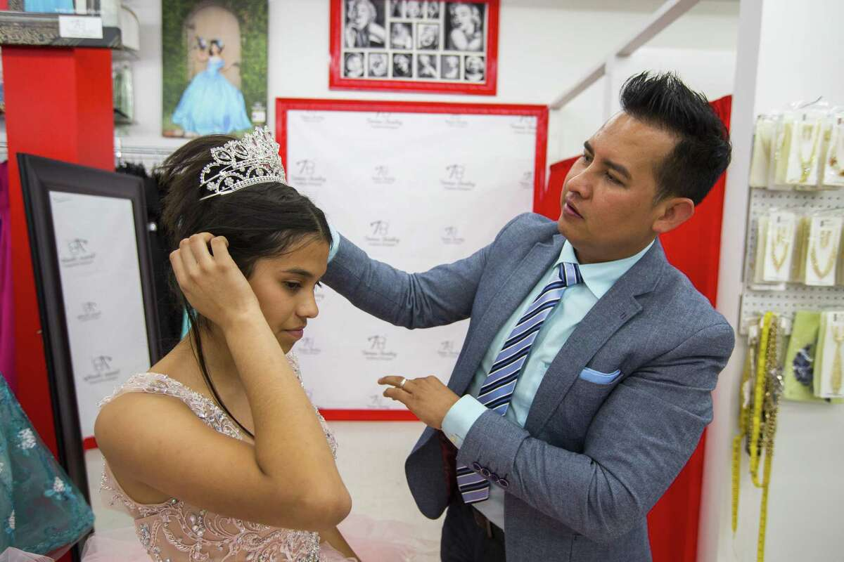 Lizbeth Gutierrez, 14, tries on a dress with designer Tomas Benitez, Wednesday, May 10, 2017, in Houston.