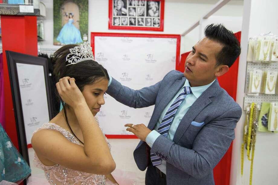 Lizbeth Gutierrez, 14, tries on a dress with designer Tomas Benitez, Wednesday, May 10, 2017, in Houston. Photo: Mark Mulligan, Houston Chronicle / Houston Chronicle / © 2017 Houston Chronicle