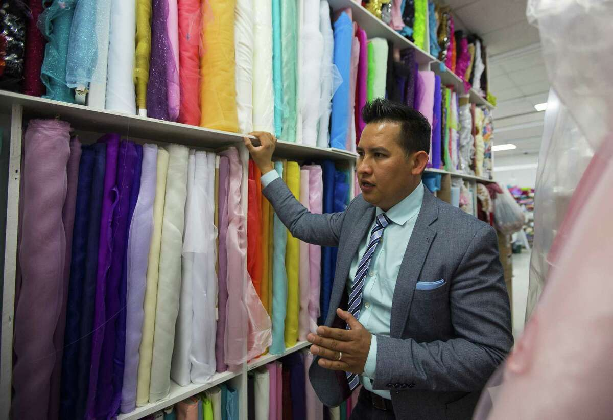 Tomas Benitez sorts through fabric inside his dress shop on Bellaire Blvd., Wednesday, May 10, 2017, in Houston.