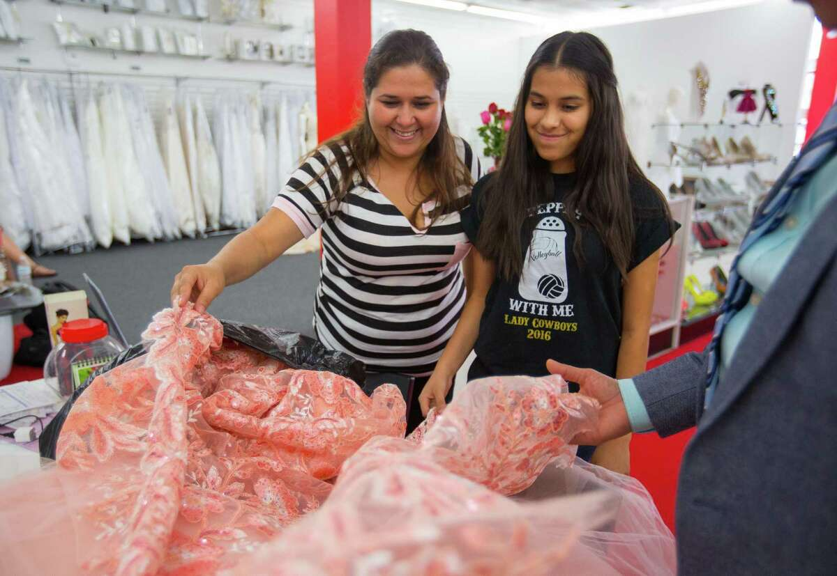 Lizbeth Gutierrez, 14, looks at the quinceañera dress fabric Tomas Benitez has put in front of her while getting ideas for the dress he is going to make her at his dress shop in Bellaire, Wednesday, May 10, 2017, in Houston. Benitez is gifting a dress to Gutierrez.