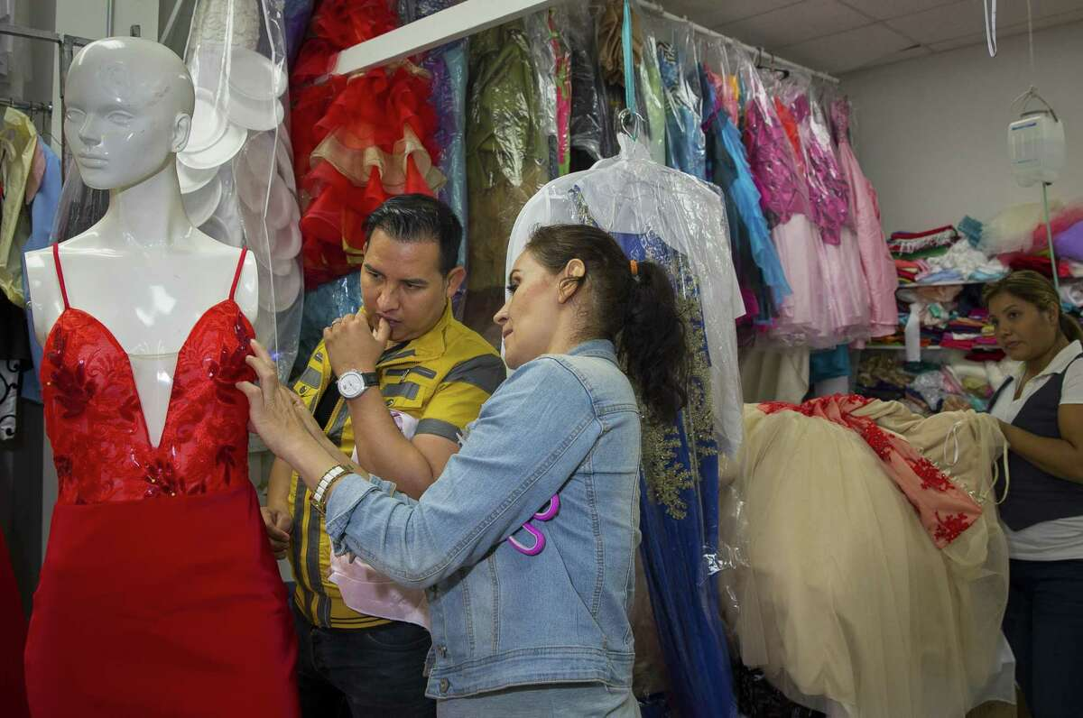 Tomas Benitez (in yellow) looks at the fit of a dress while working in his shop on a quinceañera dress for Lizbeth Gutierrez, Wednesday, Nov. 1, 2017, in Houston.