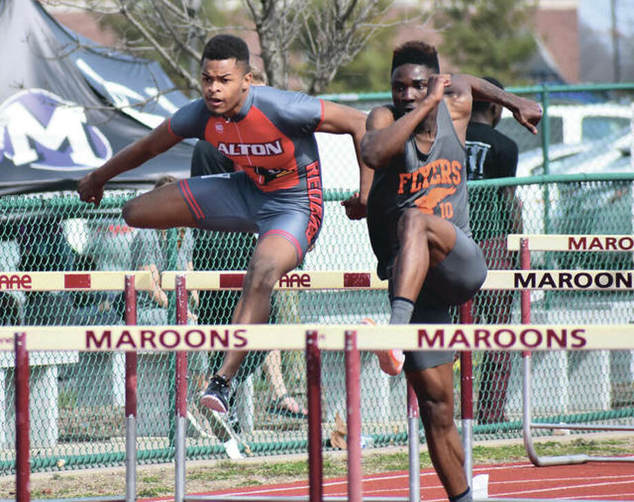 Alton's Johnathan Bumpers (left) clears a hurdle alongside East St. Louis' Andrew Johnson on Wednesday at Belleville West's Norm Armstrong Invitational boys track meet in Belleville. Bumpers place first in the 300-meter intermediate hurdles with a time of 39.35 seconds. Johnson ran seventh in the finals. It was makeup date for the Invite that attracted 18 teams after 35 were scheduled to run Saturday. Minooka scored 119 points to beat out Southwestern Conference members Edwardsville (90.5) and East St. Louis (81.5). O'Fallon (69), Cahokia (54), Alton (48), West (43), Collinsville (34), Normal West (33) and Mascoutah (31) rounded out the top 10. The Redbirds also got a runner-up performance from Ahmad Sanders, who jumped 21 feet, 6 inches in the long jump. Edwardsville's Franky Romano won the 800 meters in 2:00.17 and the Tigers got second-place finish from Roland Prenzler in the 1,600 (4:30.89), Amari Brooks in both the shot put (51-4.5) and discus (148-2) and the 4x800 relay of Romano, Prenzler, Jack Pifer and Wyatt Hennig in 8:14.64. Photo:       Matthew Kamp / Hearst Newspapers
