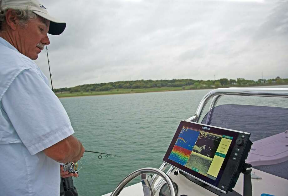 Capt. Steve Nixon watches schools of white bass on his fish finder while getting a rod ready to place in a downrigger for trolling at Canyon Lake. Photo: John Goodspeed /For The Express-News