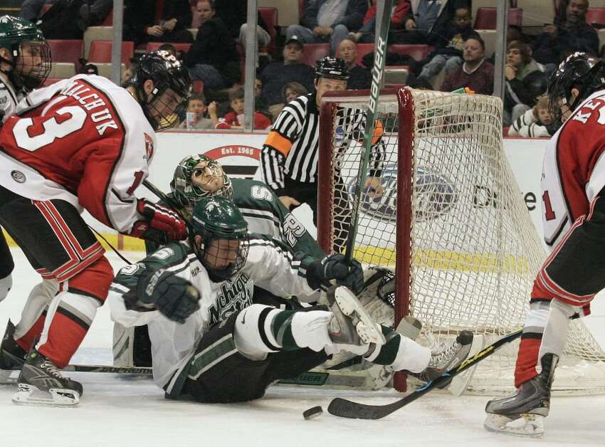 Michigan State's Andrew Rowe, center, blocks the goal during an RPI offensive surge. (AP Photo/Jerry S. Mendoza)