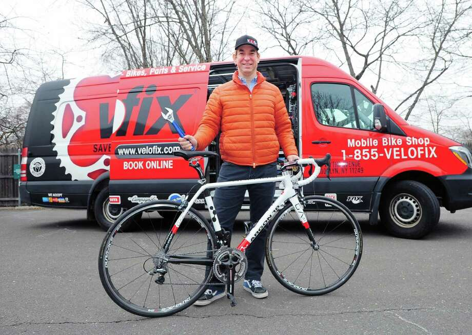Sebastiaan Pol, owner of Velofix New York Metro, with a racing bike and holding a wrench standing in front of his company's mobile bike shop vehicle in a business park in Old Greenwich, Conn., Tuesday, March 27, 2018. Velofix bills itself as a convenient bike shop experience that comes to the customer. Photo: Bob Luckey Jr. / Hearst Connecticut Media / Greenwich Time