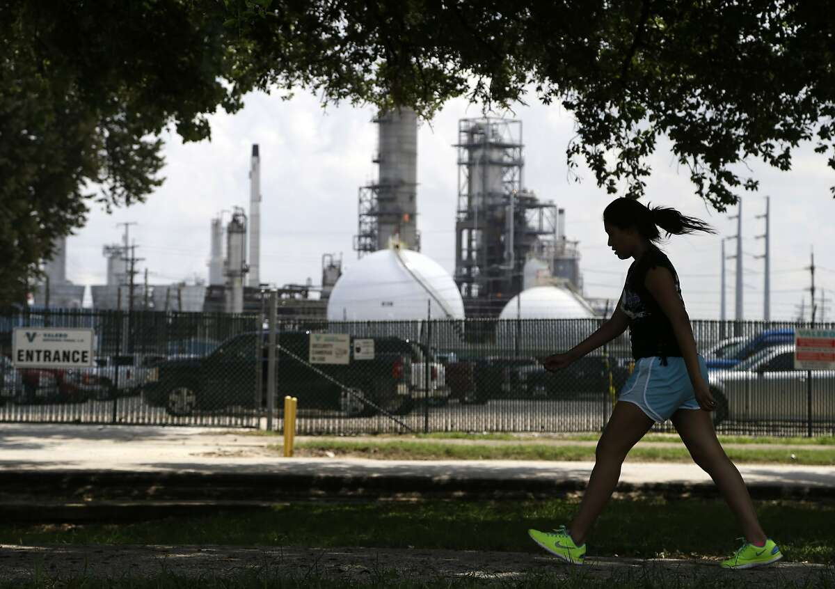 A teenage girl walks around the track of a park across the street from the Valero refinery Monday, Aug. 4, 2014, in the Manchester neighborhood of Houston. NEXT: See the world's largest oil refineries.