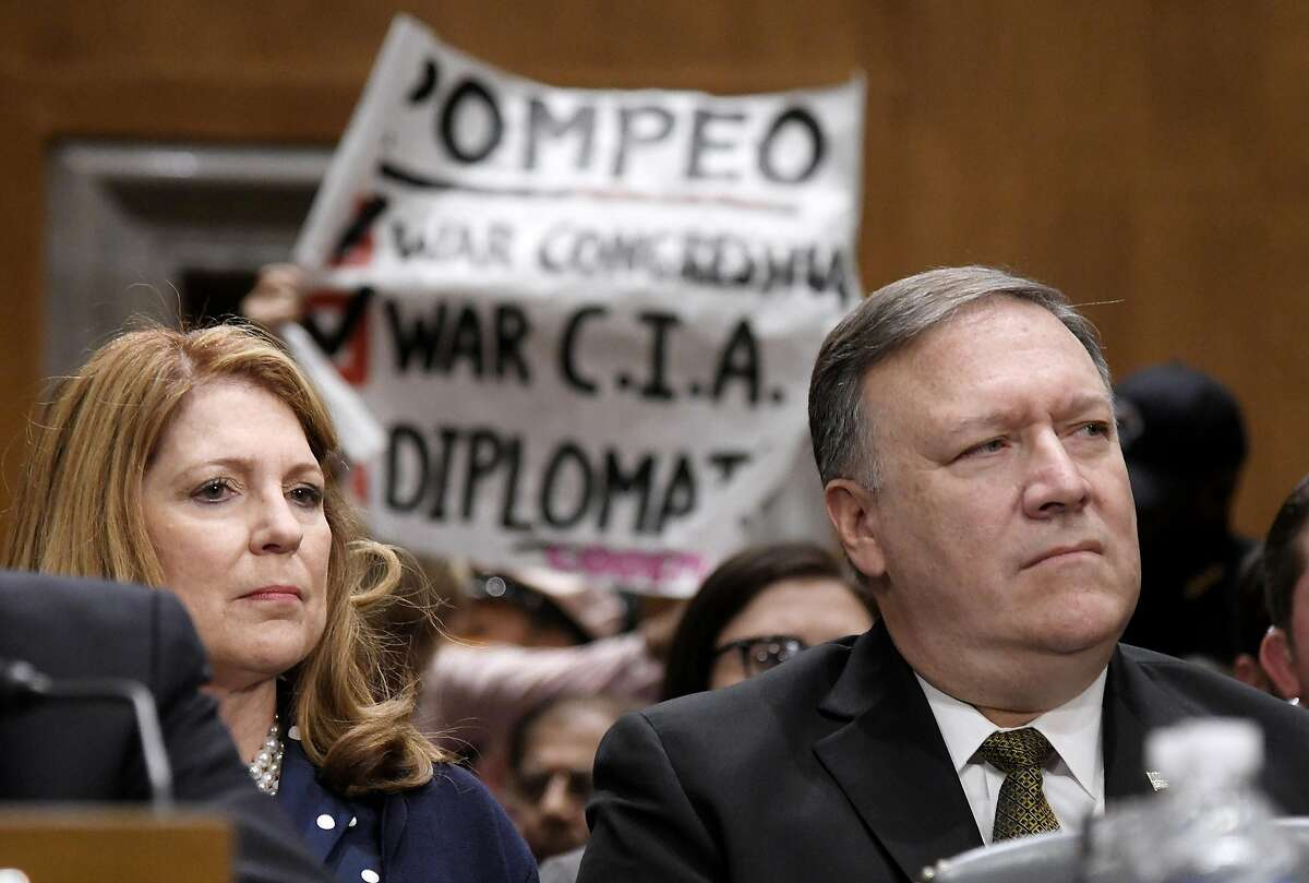 Code Pink activists hold placards to protest the nomination of Mike Pompeo, right, President Donald Trump's pick to replace former Secretary of State Rex Tillerson, during a Senate Foreign Relations Committee hearing on April 12, 2018 in Washington, D.C. (Olivier Douliery/Abaca Press/TNS)