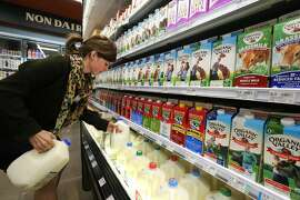 FILE - In this May 23, 2014 file photo, grocery and dairy assistant Reyna DeLoge stocks dairy products at Vitamin Cottage Natural Grocers, in Denver. After a record year for milk sales in 2014, dairy farmers face a glut. Already disheartened, farmers say they worry as futures markets predict dwindling prices in 2015. But in the dairy aisle shoppers are milking savings. (AP Photo/Brennan Linsley, File)