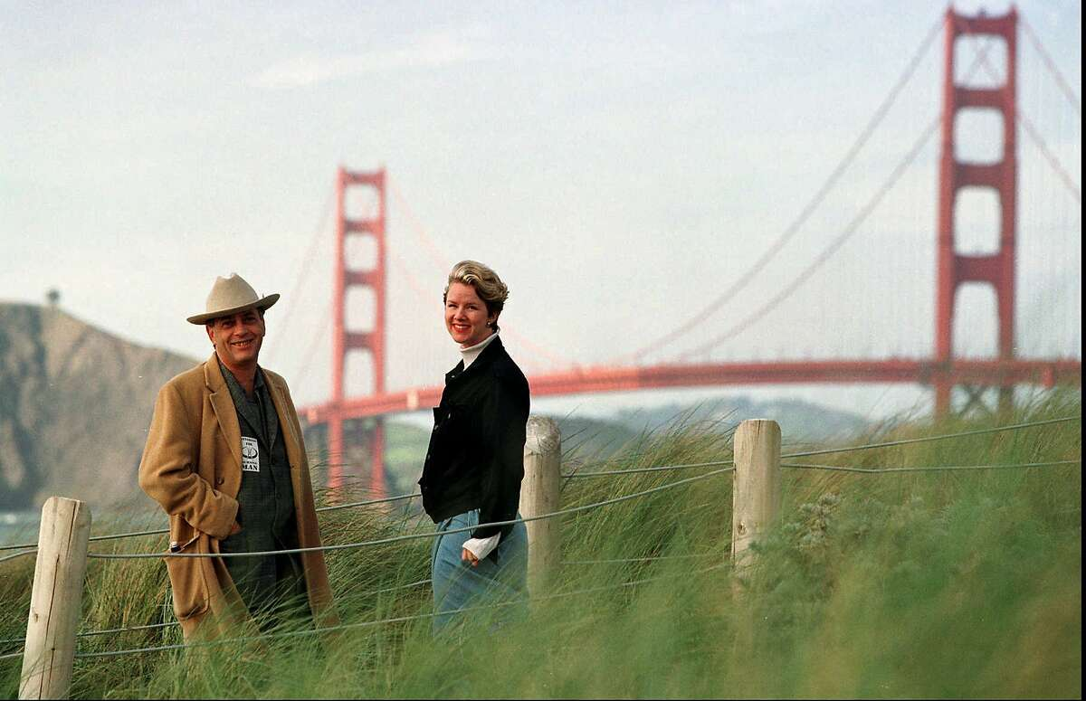 Larry Harvey, left, and Marian Goodell, two of the founders of the Burning Man festival walk near Baker Beach in San Francisco with the Golden Gate Bridge in the background Monday March 30, 1998. The first Burning Man was held at Baker Beach in 1986 with a small group of people. Last year's event drew some 15,000 to the Black Rock Desert in Nevada.