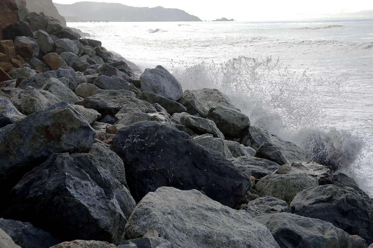Sea water splashes up against rocks near an eroding cliff in Pacifica, California, on Monday, Jan. 25, 2016.