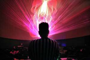 Local music artist and DJ Stastia Irons, aka Stas THEE Boss, performs during a laser light show at the Pacific Science Center, April 5, 2018.