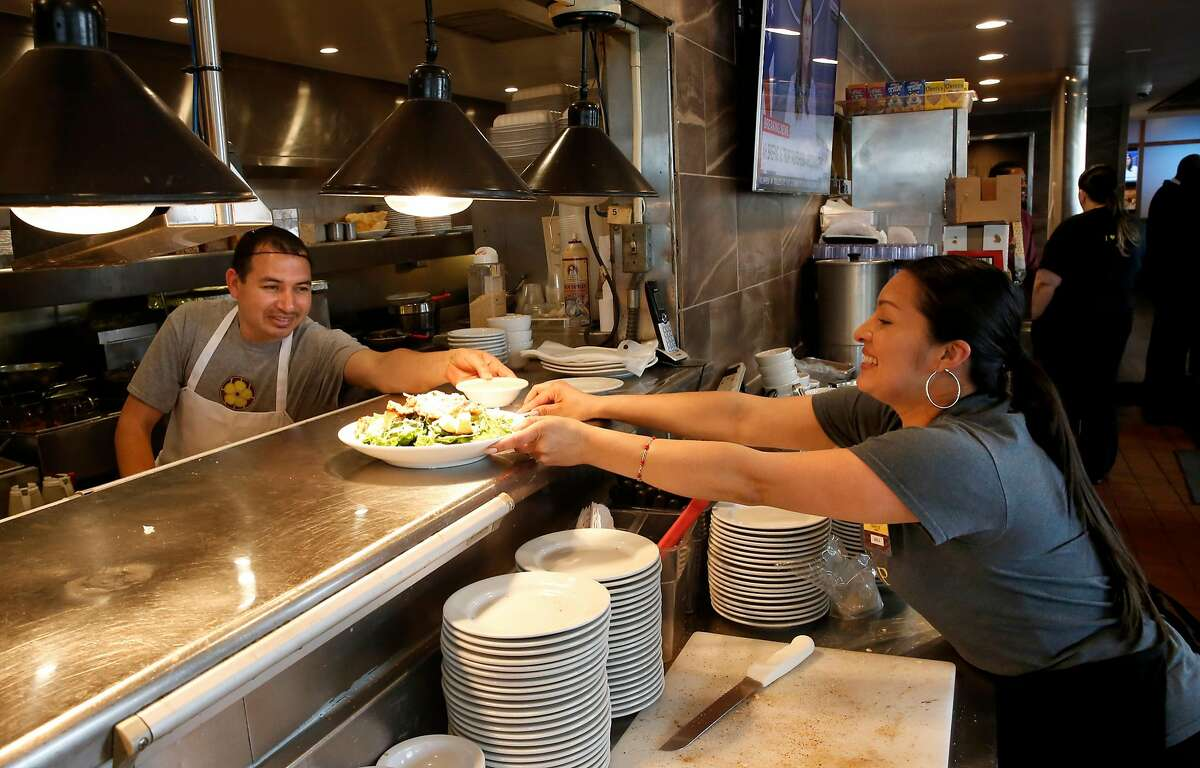 Line cook Victor and server Maricruz work the lunchtime crowd at the Buttercup Diner in downtown Oakland, Calif. on Wed. April 11, 2018. A new federal law about to go into effect would allow tips to be shared with cooks and dishwashers, could change the way the restaurant industry in California operates.