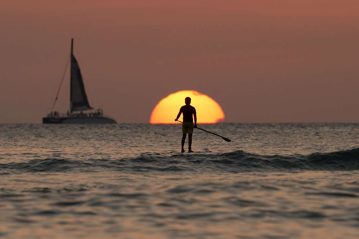 A paddleboarder looks our over the Pacific Ocean as the sun sets off of Waikiki Beach, in Honolulu.
