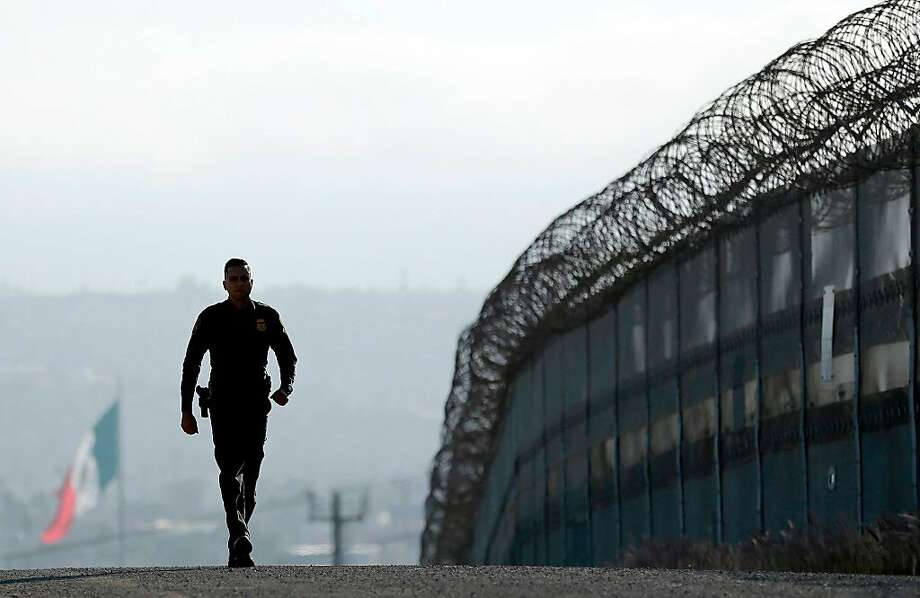 A U.S. Border Patrol agent walking near the fence separating Tijuana and San Diego in 2016. Photo: Gregory Bull / Associated Press