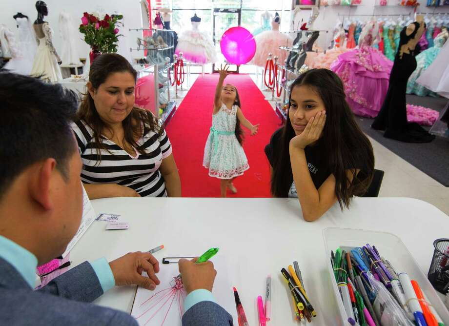 Lizbeth Gutierrez (right), 14, shops for a quinceanera dress at the Bellaire shop of designer Tomas Benitez with her mother and little sister, Wednesday, May 10, 2017, in Houston. Benitez is gifting a dress to Gutierrez. Photo: Mark Mulligan, Mark Mulligan / Houston Chronicle / 2017 Mark Mulligan / Houston Chronicle