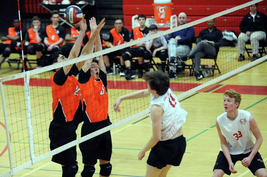 Stamford High School players James Pease, far left, and Adam Piersa rise while attempting to block New Canaan's Camden Nelson from spiking the ball during a boys varsity volleyball match inside the New Canaan gymnasium in New Canaan, Conn. on Thursday, April 12, 2018. Photo: Michael Cummo / Hearst Connecticut Media / Stamford Advocate