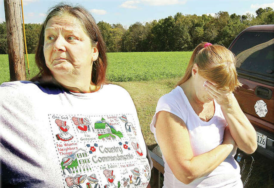 The family of Bonnie Woodward has been waiting a long time for answers. In this photo taken in late September 2010, Linda Dean, left, and Bobbie Valdes, right, both sisters of Woodward, who at the time had been missing since June 25 of that year, react with emotion while they wait for word from the 80 law enforcement officers who were searching for her body around the home of Roger Carroll, then 44, on Creek Road east of Jerseyville. Photo:     John Badman   The Telegraph