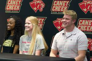 Caney Creek's Keyanah Browning, Erica Strawn and Marcus Garza signed National Letters of Intent during a spring signing ceremony at Caney Creek High School, Thursday, April 12, 2018, in Grangerland.