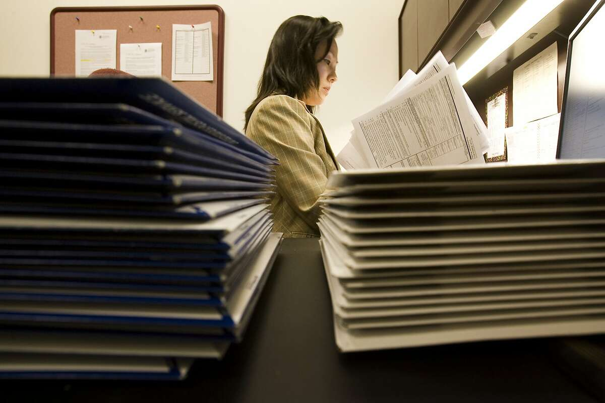 Paralegal Cindy Deng (cq) prepares a H1B Visa Application as stacks envelopes of completed forms sit on her desk at Epstein, Becker, Green, Wickliff & Hall, in downtown Houston, Friday afternoon, March 30, 2007. The first day you can file these applications is April 2 and visas, used by immigrants who work as teachers, engineers, doctors and other professionals are issued on a first come, first serve basis. (Smiley N. Pool / Chronicle)