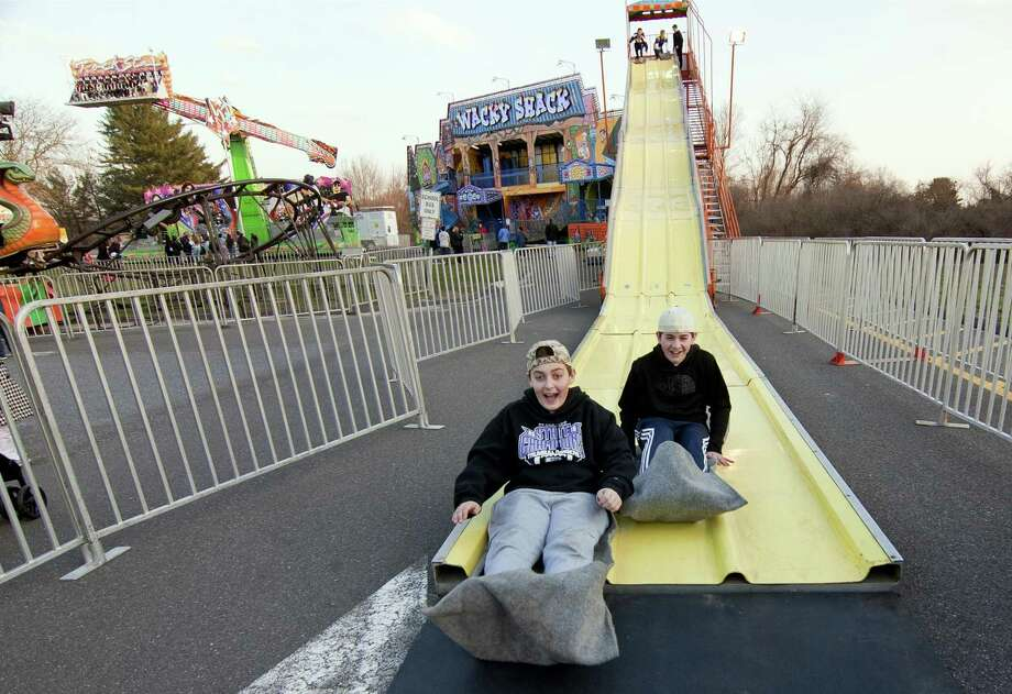 Anthony Guarino, 13, at left, and his buddy Scott Gell, 13, both of Trumbull, reach the end of the Super Slide during the annual Trumbull Rotary Carnival at Hillcrest Middle School in Trumbull on Wednesday.The carnival, which raises money for service projects and grants continues through Sunday. Photo: Christian Abraham / Hearst Connecticut Media / Connecticut Post