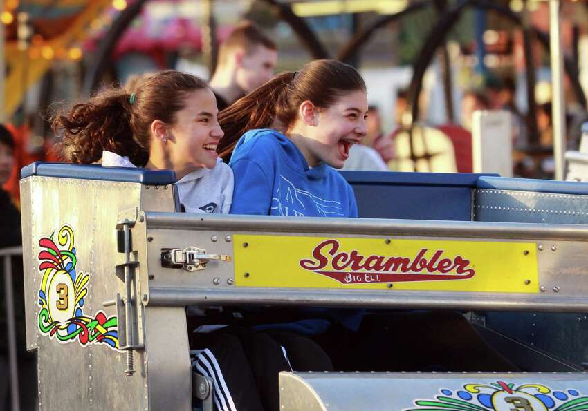 Sophia Bennett, 11, at left, and her friend Maddy Farasciano, 11, ride The Scrambler during the annual Trumbull Rotary Carnival at Hillcrest Middle School in Trumbull on Wednesday. The carnival, which raises money for service projects and grants, continues through Sunday.