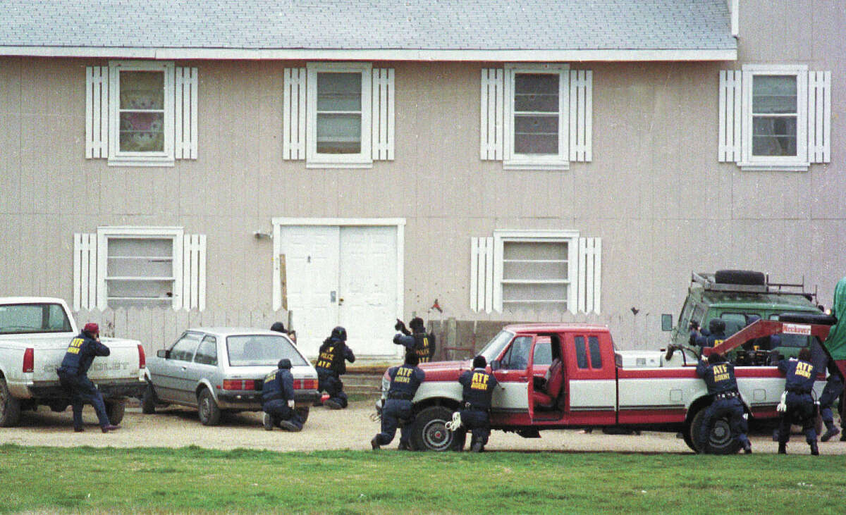 Federal Alcohol Tobacco and Firearms agents approach the front door of the Branch Davidian compound near Waco, Texas, in this Feb. 28, 1993, file photo, in an attempt to serve a search warrant. Four agents and five Davidians were killed in the shootout that marks its 25-year anniversary this month. (AP Photo/Waco Tribune Herald, Rod Aydelotte, File)