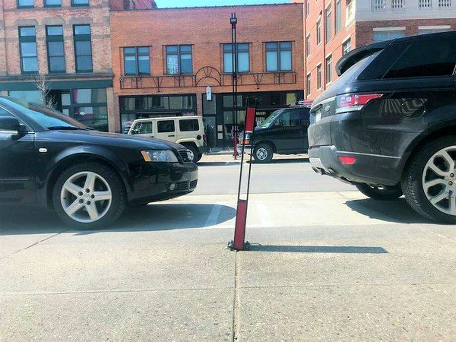 Bolts connect a crooked parking bollard to cement on Main Street on April 12. The city is considering ways to either strengthen the parking dividers, increase their height or remove them altogether after at least 12 have been run over by cars.