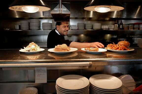Line cook Barraza prepares lunchtime dishes the Buttercup Diner in downtown Oakland, Calif. on Wed. April 11, 2018. A new federal law about to go into effect would allow tips to be shared with cooks and dishwashers,  could change the way the restaurant industry in California operates.