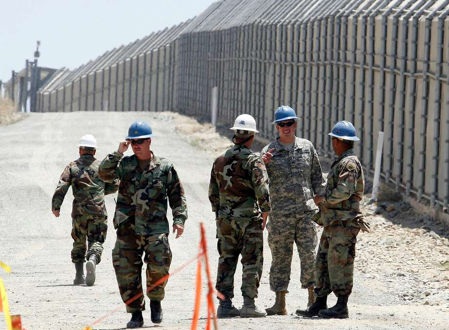 In this June 21, 2006, file photo, members of the California National Guard work next to the U.S.-Mexico border fence near the San Ysidro Port of Entry in San Diego. Photo: Denis Poroy, Associated Press