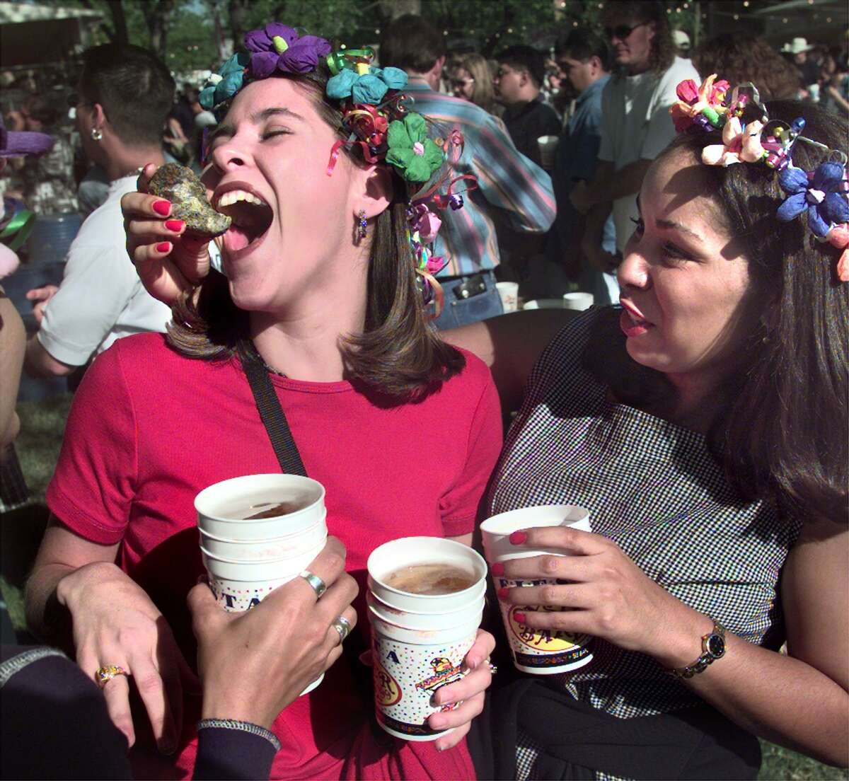 Save your cups: Wash down all that food with a cold beer - or two. Don't be surprised to see party-goers at the popular A Night in Old San Antonio event carrying stacks of empty souvenir beer cups with pride. A Fiesta-goer gets an oyster crammed in her face as she holds a stack of beer cups at the St. Mary's Oyster Bake in 1999.