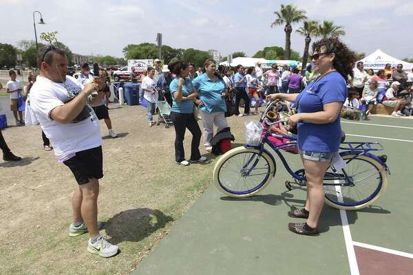 Pat Watters (left) takes a picture of Christine Jones afar she won a bicycle at the Earth Day Fiesta celebration at Woodlawn Lake April 12, 2014. The event featured food, tree giveaways and a raffle for bicycles.