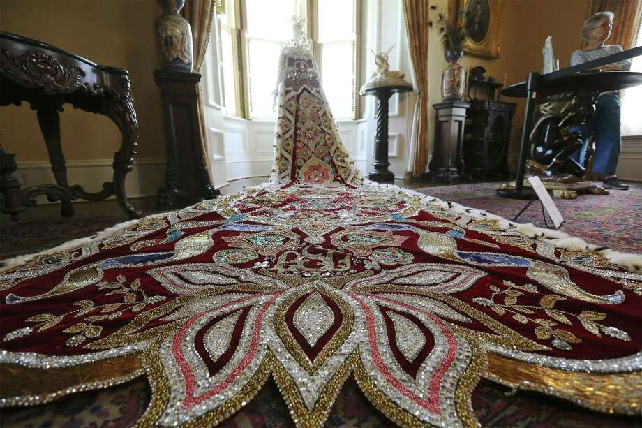 The elaborate train that weighs about 120 pounds on a dress worn by Gloria Galt Steves as Queen of Court of the Lion and Dragon from 2004 is seen on display at the Steves Homestead on Thursday. Photo: Kin Man Hui /San Antonio Express-News / ©2018 San Antonio Express-News