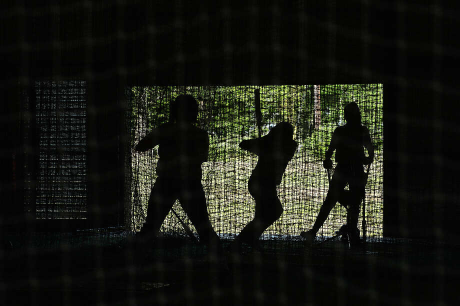 Port Neches - Groves' softball players are silhouetted as they get in batting practice at their indoor facility.   Photo taken Thursday, April 12, 2018 Kim Brent/The Enterprise Photo: Kim Brent / BEN