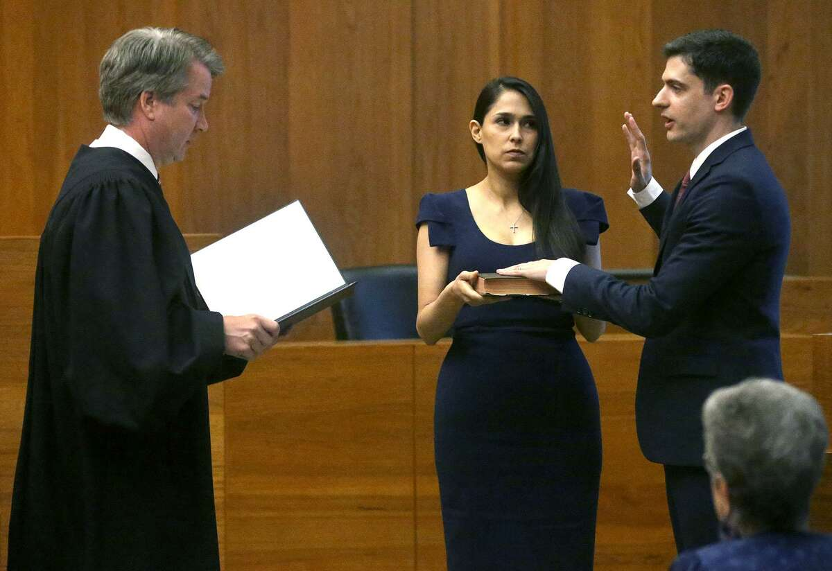 John F. Bash, right, is sworn in as U.S. attorney of the Western District of Texas by now-Supreme Court Justice Brett M. Kavanaugh. Bash's wife, Zina Bash, looks on.