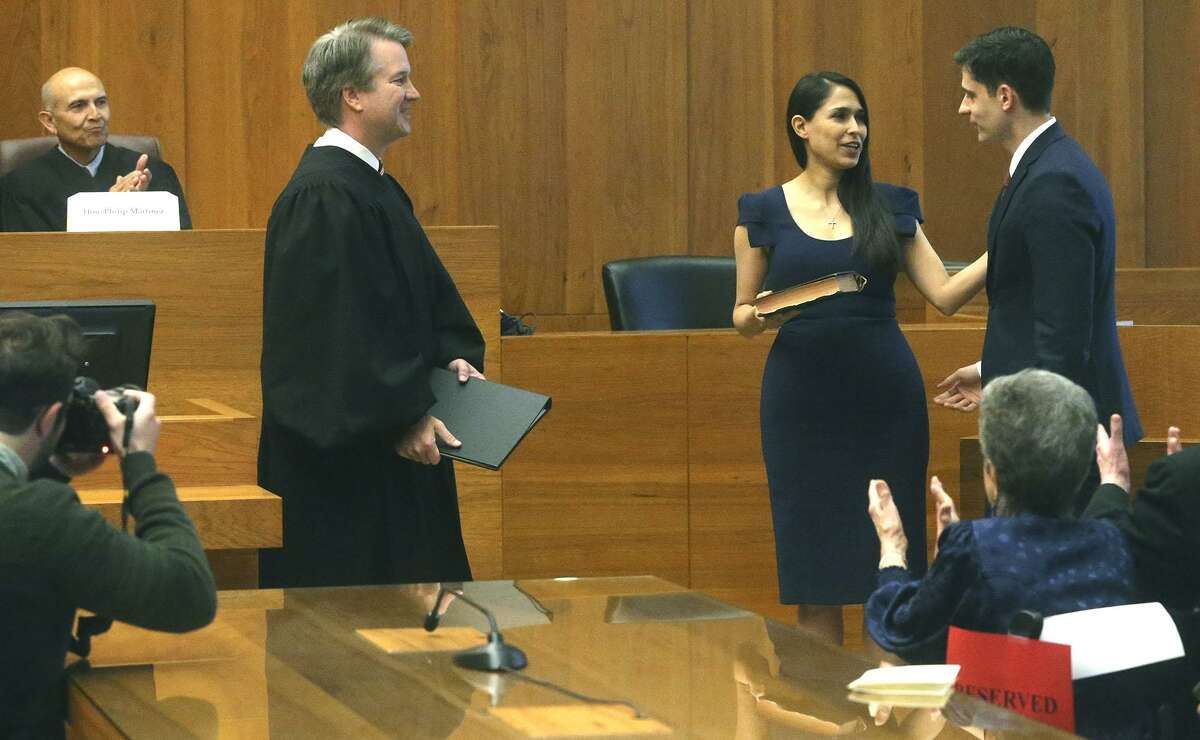 John Bash (right) is congratulated after being sworn in Thursday April 12, 2018 at the Federal Courthouse in Austin, Texas as President Trump's appointee as the new U.S. Attorney for the Western District of Texas by Brett M. Kavanaugh (left) as Bash's wife Zina Bash (center) looks on. Bash, a graduate of Harvard, clerked for the late Supreme Court Justice Antonin Scalia.