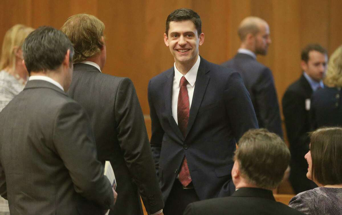 John Bash (center, facing) smiles before being sworn in April 2018 at the federal courthouse in Austin. Bash and a U.S. Attorney in Florida recently announced a $22.5 million settlement with a Belgium-based supplier of compounding medication over alleged fraud of its subsidiaries in the United States, exposed by whistleblowers in San Antonio and Florida.