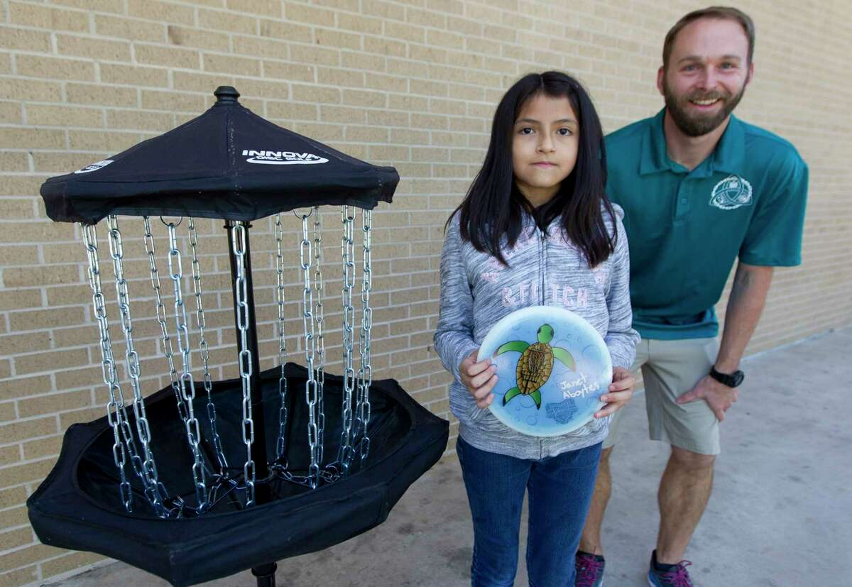 A girl in third grade at Rice Elementary third grader Janet Aboytes holds a disc with her design beside coach Cody Bearden, Wedneday, April 11, 2018, in Conroe. Aboytes' design won a worldwide Facebook contest to have her art featured on a disc used for international disc golf competition.