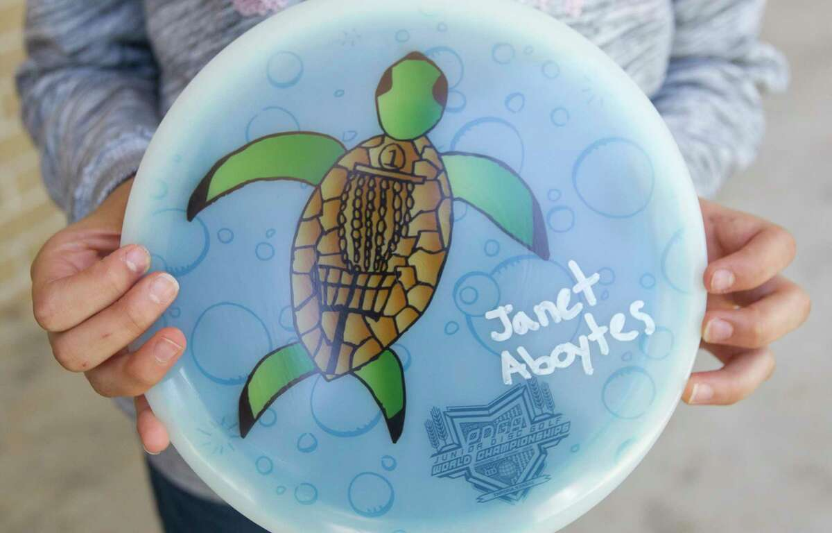 A girl in third grade at Rice Elementary third grader Janet Aboytes holds a disc of her design, which one a worldwide Facebook contest to have her art on a disc used for international disc golf competition.