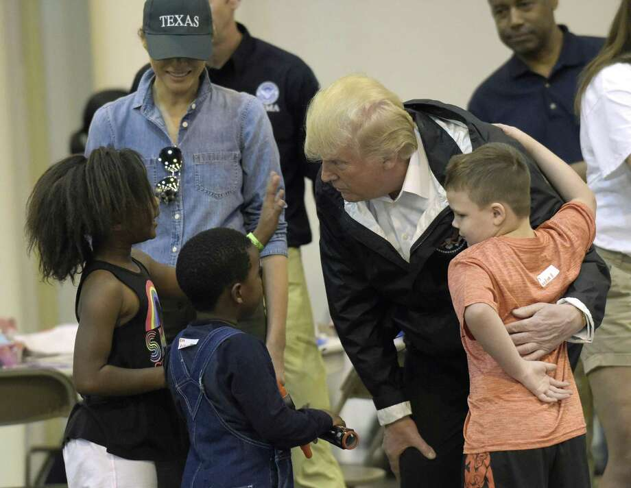 President Donald Trump meets people affected by Hurricane Harvey during a Sept. 2 visit to the NRG Center in Houston. He's returning to Houston to headline a May 14 fundraising luncheon to help Senate Republicans raise money for the 2018 midterms Photo: Susan Walsh /Associated Press / Internal