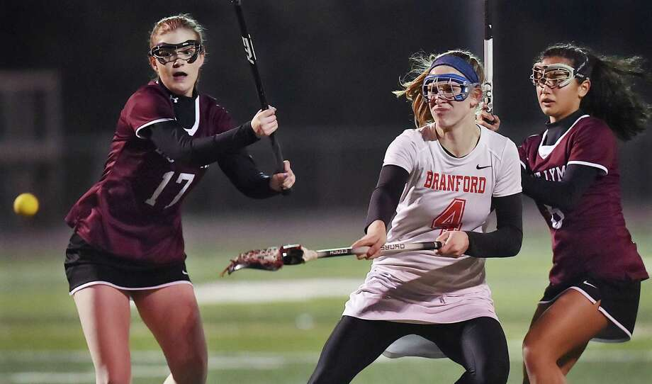 Branford senior Sophie Spencer fires a shot at the goal against East Lyme's defender Emma Locklear (17) midfielder Julia Bates (6) scoring eight goals and one assist against the Vikings at the James L. MacVeigh Alumni Athletic Complex, Thursday, April 12, 2018, at Branford High School. The Hornets won, 15-3. Photo: Catherine Avalone, Hearst Connecticut Media / New Haven Register