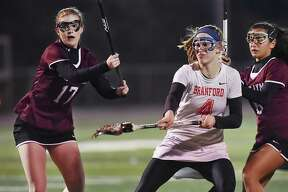 Branford senior Sophie Spencer fires a shot at the goal against East Lyme's defender Emma Locklear (17) midfielder Julia Bates (6) scoring eight goals and one assist against the Vikings at the James L. MacVeigh Alumni Athletic Complex, Thursday, April 12, 2018, at Branford High School. The Hornets won, 15-3.