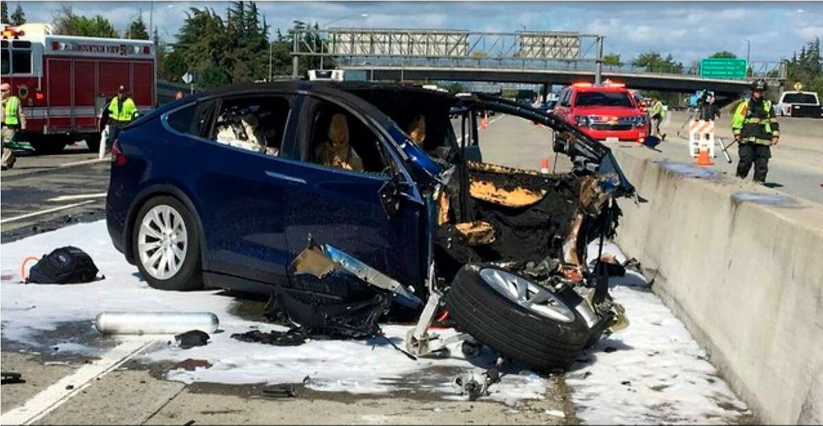 FILE - In this March 23, 2018, file photo provided by KTVU, emergency personnel work at the scene where a Tesla electric SUV crashed into a barrier on U.S. Highway 101 in Mountain View, Calif. Federal safety investigators have booted electric car maker Tesla Inc. from the group investigating a fatal crash in California that involved an SUV operating with the company's Autopilot system. The National Transportation Safety Board said Thursday, April 12, it removed Tesla as a party to the investigation after the company prematurely made information public. (KTVU via AP, File)