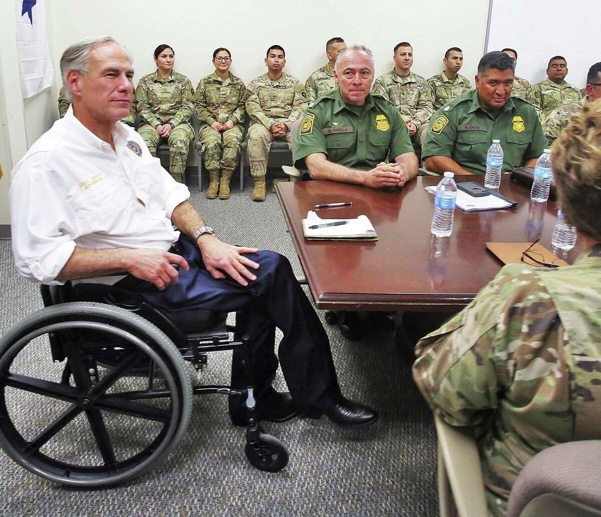 Gov. Greg Abbott, left, talks with leaders of the Texas National Guard and the Border Patrol at the Texas National Guard Armory on April 12 in Weslaco. Abbott announced that there will be an increase of 1,000 Texas National Guard on the southern border with Mexico.