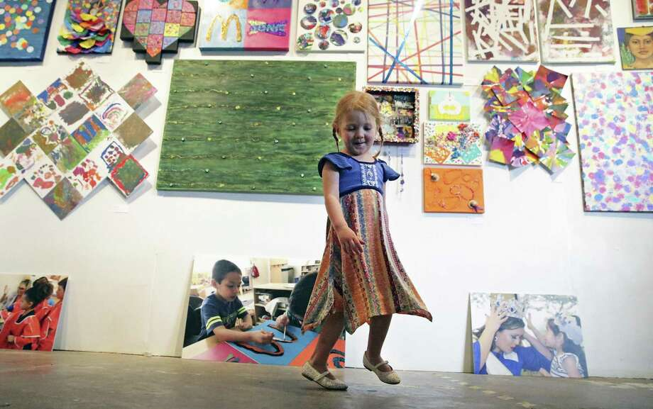 Gianna Heinrich dances in front of artwork at the Pre-K 4 SA art gallery opening at the Mercury Project, Art Gallery on April 12, 2018. Photo: Tom Reel, Staff / San Antonio Express-News / 2017 SAN ANTONIO EXPRESS-NEWS