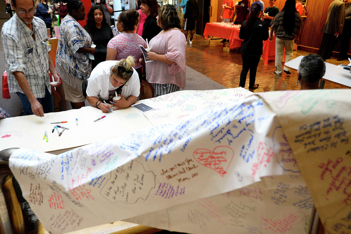Attendees write messages on a banner at the 28th Annual Crime Victim's Candlelight Vigil at the Jefferson County Courthouse. The vigil was held to remember crime victims as part of National Crime Victims' Rights Week. Photo taken Thursday 4/12/18 Ryan Pelham/The Enterprise