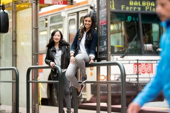 Muni Diaries co-founders Tara Ramroop, right, and Eugenia Chien pose for a portrait at a Market St. bus stop on Monday, April 9, 2018, in San Francisco.