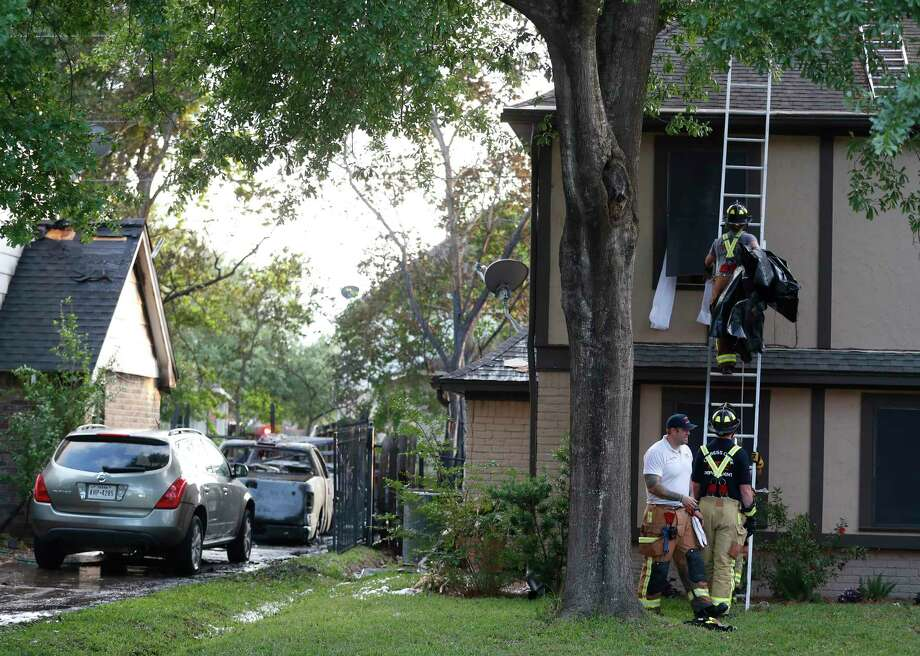 Firefighters work to clean up after battling a house fire at 14023 Cleobrook Drive, that spread to two other houses, Thursday, April 12, 2018, in Houston. Investigators are still trying to gather evidence about what started the fire. One firefighter was treated on the scene for heat exhaustion. One woman, who was asleep at the first home, was saved by a passing neighbor, who knocked on the door and got her out of the home. Photo: Karen Warren, Houston Chronicle / © 2018 Houston Chronicle