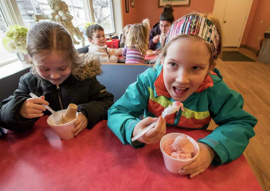 Molly Bardin, 7, and her sister Anna Bardin, 8, enjoy their ice cream at DeVoe's Rainbow Delights on opening day Thursday, April 12, 2018,  in Clifton Park, N.Y. (Skip Dickstein/Times Union) Photo: SKIP DICKSTEIN / 20043483A